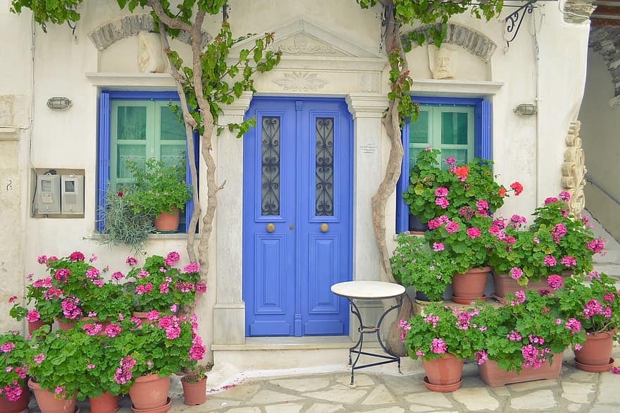 greek island door tinos island pyrgos dor with flowers windows traditional tiniotic house house with flowers in front house with table in front tourist destination landscape