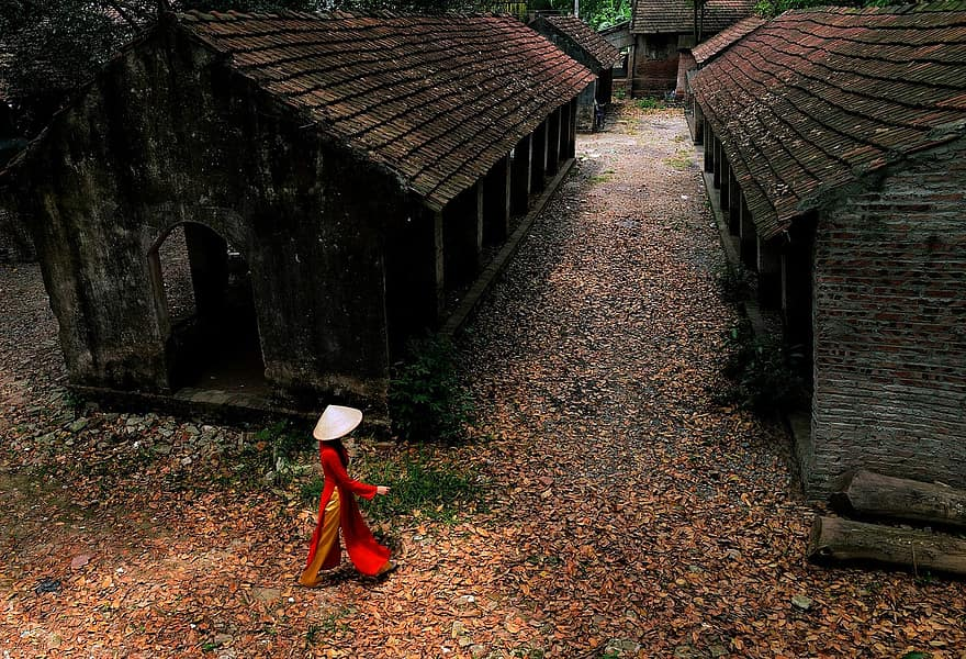 person woman walking houses huts wooden old village leaves