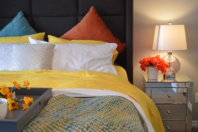 bed bedroom lamp bedside pillows lighting interior room house