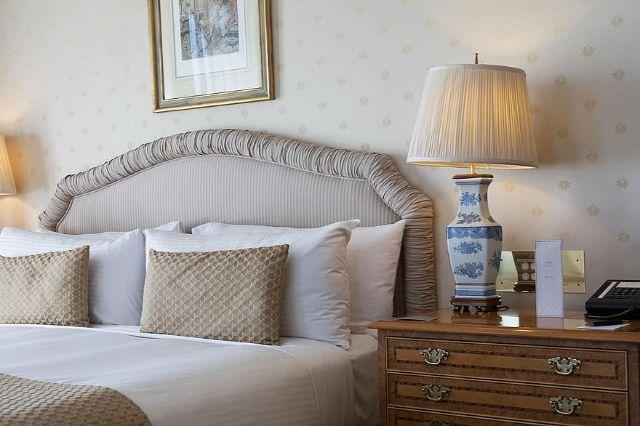 furniture room pillow lamp bedroom hotel suite bed bedside table