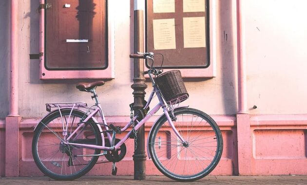pink wall bike bicycle outside window sidewalk pole chain