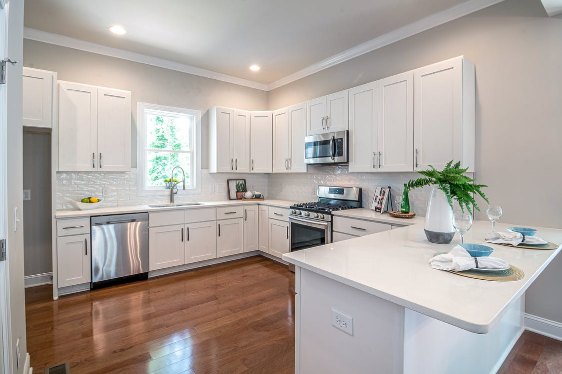 do kitchen cabinets go on top of flooring
