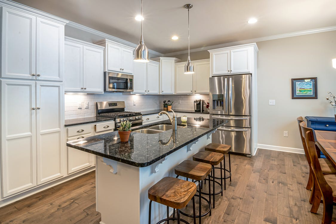 do kitchen cabinets sit on top of flooring